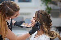Vue du côté du maquilleur faisant le visage à la femme dans le salon de beauté photographie stock
