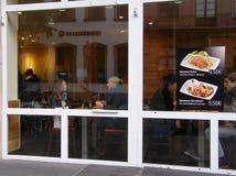 Vue du café par le verre de fenêtre, les personnes Image libre de droits