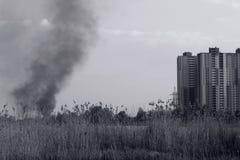 Vue du feu et de la fumée noire près des bâtiments résidentiels dans la ville problème social de concept de pollution environneme photo libre de droits