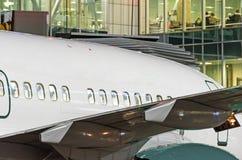 Vue du fuselage d'un avion de transport de passagers avec des hublots sur le fond du terminal en verre du ` s d'aéroport la nuit Photo stock