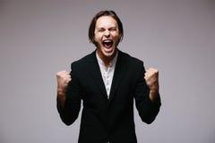 Vue du jeune homme d'affaires enthousiaste maintenant des bras augmentés et exprimant la positivité Photo stock