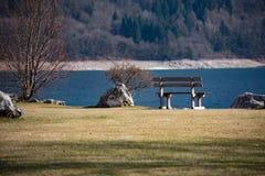 Vue du lac Molveno avec le banc sur la pelouse, photo stock