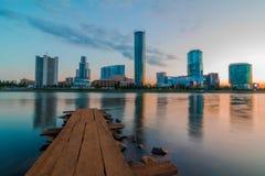 Vue du pilier en bois sur l'étang de ville et les gratte-ciel de Yeka photos libres de droits