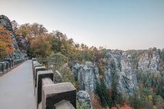 Vue du pont de Bastei sur les montagnes de chope en grès d'Elbsand dans l'humeur d'automne avec des arbres et la formation de roc photo stock