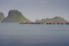Vue du pont de mer et de Mer Rouge avec un bateau s'étendant près d'un pont, montagne à l'arrière-plan, moment de coucher du sole Photographie stock libre de droits