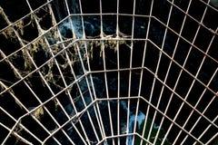 Vue du renfort en métal sous forme de Web contre l'ouverture, le soleil au coucher du soleil photos stock