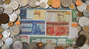 Vue du sort de pièces de monnaie de différents pays du monde désordonné sur de vieux billets de banque à l'arrière-plan photos stock