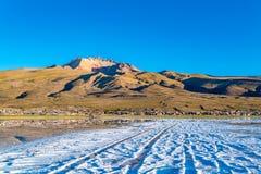 Vue du volcan dormant Tunupa et du village de Coqueza ? l'appartement de sel d'Uyuni image stock