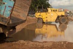 Vue du WS des véhicules boueux inondés de constructon de bord de la route avec Images stock
