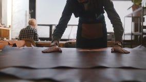 Vue en gros plan d'artisan professionnel répandant un grand morceau de cuir dans le mouvement lent de fabrication moderne d'ateli banque de vidéos