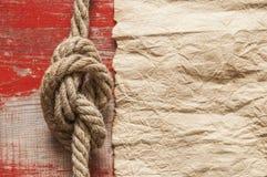 Vue en gros plan d'un noeud de mer de corde sur le rétro fond de papier souillé jaune photographie stock