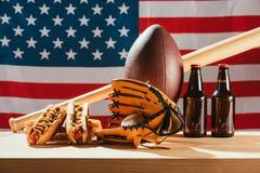 vue en gros plan de bière avec les hot-dogs et l'équipement de sport avec le drapeau américain Photographie stock