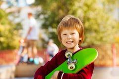 Vue en gros plan de garçon de sourire avec la planche à roulettes verte Photographie stock libre de droits
