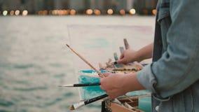 Vue en gros plan de jeune femme tenant les brosses et dessinant la photo sur le rivage du lac michigan, Chicago, Amérique banque de vidéos