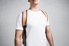Vue en gros plan de jeune type élégant dans le T-shirt et le sac à dos blancs vides image libre de droits
