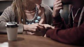 Vue en gros plan de jeunes beaux couples se reposant dans le café, le café potable et parlant, passant le temps ensemble clips vidéos