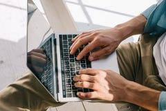 Vue en gros plan de l'homme dactylographiant sur le clavier d'ordinateur portable photos stock