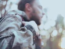 Vue en gros plan de l'homme dans le camouflage fermant la fermeture éclair une veste Mâle de touristes avec le sac à dos passant  banque de vidéos