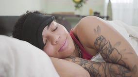Vue en gros plan de la femme adorable d'Afro-américain se trouvant sous la couverture blanche avec le masque noir de sommeil Repo banque de vidéos