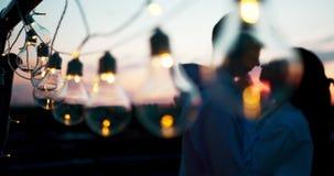 Vue en gros plan de la ficelle des lumières au fond brouillé des couples affectueux de baiser pendant le coucher du soleil banque de vidéos