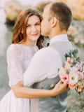 Vue en gros plan de la jeune mariée tenant le bouquet tandis que le marié l'embrasse sur la joue Composition en mer Photo libre de droits