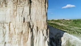 Vue en gros plan de la pente blanche de falaise de soulagement avec le beau pré vert sur le fond dans le jour d'été chaud contre banque de vidéos