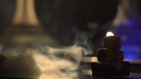 Vue en gros plan de la pyramide de trois braises au fond brouillé de couleurs changeantes des narguilés La fumée énorme clips vidéos