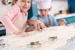 vue en gros plan de pâte et de formes crues pour des biscuits et de petits enfants mignons Photographie stock
