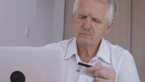 Vue en gros plan de shoping en ligne d'homme supérieur à la maison sur l'ordinateur portable, numéro de carte de dactylographie d banque de vidéos