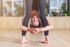 Vue en gros plan de yogi féminin avec sa tête entre les jambes tout en se tenant dans la pose de recourbement en avant de yoga à  Photos stock