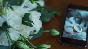 Vue en gros plan des anneaux de mariage au téléphone portable avec la photo des couples affectueux sur le papier peint se trouvan banque de vidéos