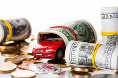 vue en gros plan des billets de banque roulés du dollar, du petit modèle rouge de voiture et des bitcoins Photographie stock