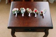 Vue en gros plan des cinq boutonnieres des roses coloutful sur la table Photographie stock libre de droits