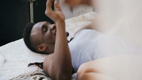 Vue en gros plan des couples multiraciaux sur le lit, combat par des oreillers Femme s'asseyant sur l'homme, ayant l'amusement en banque de vidéos