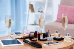 vue en gros plan des dispositifs numériques, des verres de champagne et des divers cosmétiques images stock