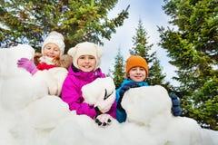 Vue en gros plan des enfants heureux derrière le fort de neige Photos stock