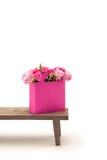 Vue en gros plan des fleurs roses de floraison d'offre dans le sac de papier rose sur le banc en bois Image stock
