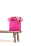 Vue en gros plan des fleurs roses de floraison d'offre dans le sac de papier rose sur le banc en bois Photos stock