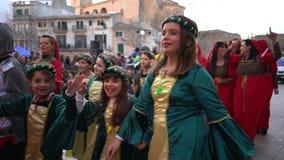 Vue en gros plan des jeunes et adultes dans différents costumes de ressortissant et de carnaval marchant et dansant sur la rue banque de vidéos