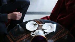 Vue en gros plan des mains des couples dans le café Ils boivent du thé et mettent des tasses en place banque de vidéos