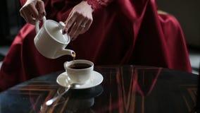 Vue en gros plan des mains de la femme dans le thé se renversant rouge dans la tasse et le boire Emplacement de café clips vidéos
