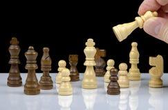 Vue en gros plan des pièces d'échecs avec la réflexion sur le fond blanc avec la main jugeant la reine d'isolement Images stock