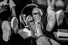 Vue en gros plan des pieds du ` s de femme dans des chaussures élégantes avec des écouteurs sur la table en bois Photo stock