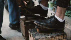 Vue en gros plan des pieds masculins sur un support Chaussez le menhaden travaillant à la rue, polissant les chaussures de noir d banque de vidéos