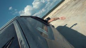 Vue en gros plan du côté de la voiture russe noire se déplaçant sur la surface arénacée avec l'homme regardant hors de la voiture clips vidéos