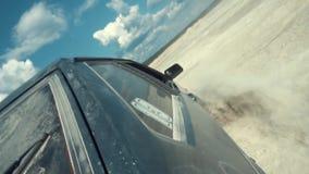 Vue en gros plan du côté de la voiture russe noire se déplaçant sur la surface arénacée contre le ciel nuageux bleu longueur Emba banque de vidéos