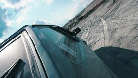 Vue en gros plan du côté de la voiture russe noire se déplaçant sur la surface arénacée contre le ciel nuageux bleu longueur Emba clips vidéos