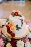 Vue en gros plan du gâteau de mariage décoré des roses colorées Photos stock