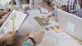 Vue en gros plan du groupe de personnes de métis travaillant à la table Équipe discutant la conception architecturale, compagnie  Photographie stock libre de droits