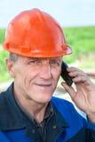 Vue en gros plan du travailleur manuel mûr dans le masque invitant le téléphone Images stock